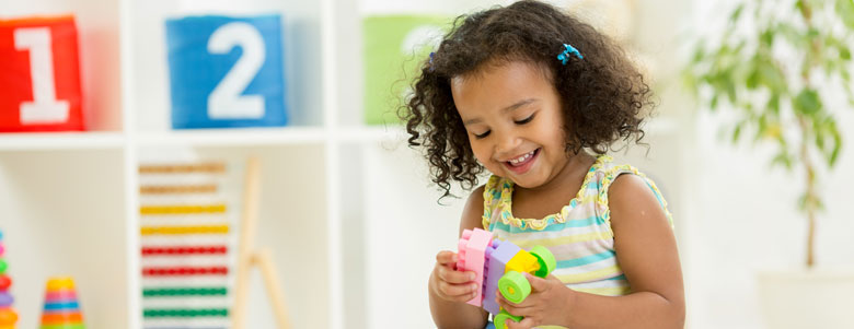 Smiling girl playing with toys